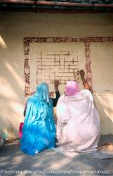 Women painting the walls of their home, India Gujerat