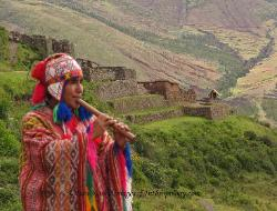 Quechua flute player, Inca ruins of Pisac in the background, Andes Mts, Peru